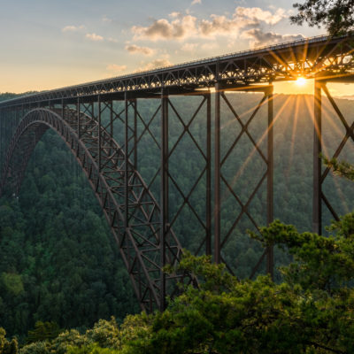 Setting sun behind the girders of the high arched New River Gorge bridge in West Virginia